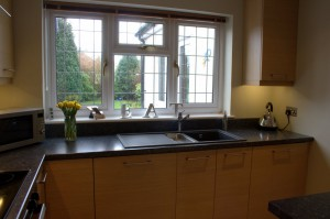 View of Oak kitchen with black Franke sink