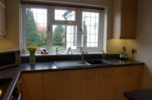 View of Oak kitchen with black Franke sink